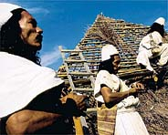 Two Arhuaco men help a third build his matrimonial house. Arhuaco custom holds that marriage ceremonies should not take place until the couple's home is completed.